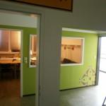 Flur mit Blick auf Büro/Lounge und hell erleuchtetem Labor